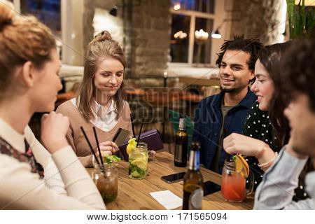 leisure, people and holidays concept - happy friends with drinks, credit card and bill at bar or cafe