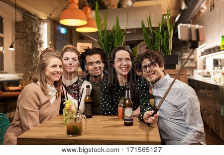 leisure, technology, friendship, people and holidays concept - happy friends with drinks and taking picture by smartphone selfie stick at bar or cafe