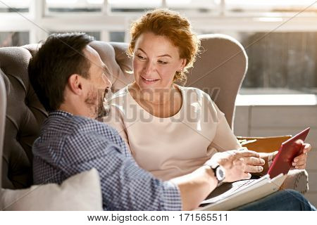 Romantic atmosphere. Happy glad cheerful middle aged couple sitting at home on the couch and using the laptop while expressing positivity and happiness