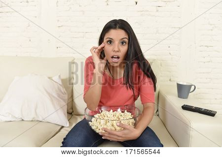young beautiful Spanish woman in jeans home alone watching television sitting at sofa couch on living room excited enjoying suspense movie or series having fun intense surprised eating popcorn
