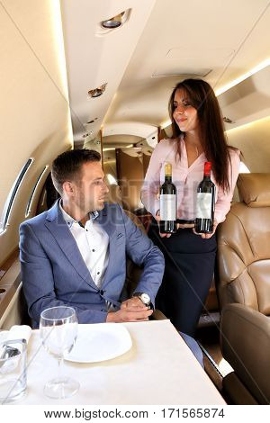 Flight attendant offering the wine to young passenger of business jet