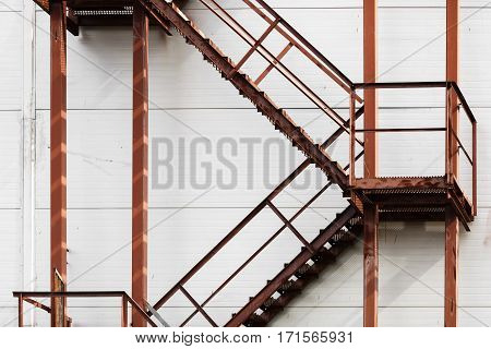 Old rusty metal ladder against a white wall background. Metal steps with handrails and staircases covered with rust. Facade of industrial buildings.