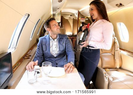 Young man on board the small jet plane before having dinner