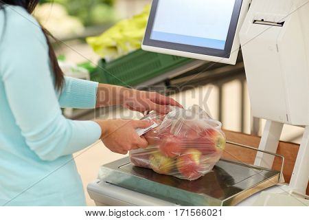shopping, sale, consumerism and people concept - woman weighing apples on scale at grocery store