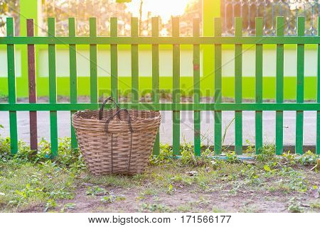 Weave trash basket Dustbin made from bamboo weaving on grass field. fence background. under sun light.