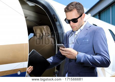 Man with mobile phone and tablet standing in door of small jet plane