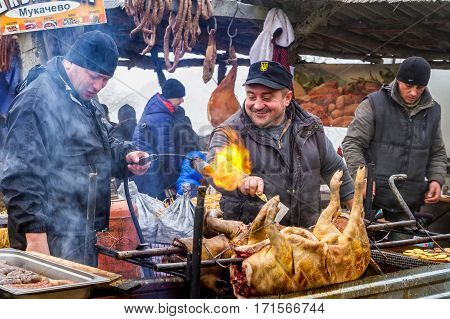 Hecha Ukraine - February 11 2017: Chefs one of the teams of butchers fry the pigs on a spit during the 11th International gastronomic festival in the village butchers Hecha.