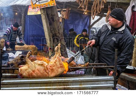 Hecha Ukraine - February 11 2017: Cook one of the teams of butchers fry the pig on a spit during the 11th International gastronomic festival of butchers in the village Hecha.