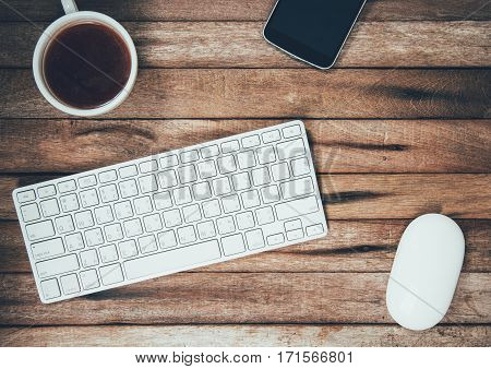 Creative vintage workspace table with key board mouse coffee and smart phone top view with Copy Space on vintage background.
