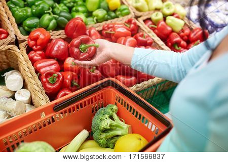 sale, shopping, food, consumerism and people concept - woman with basket buying bell peppers or paprika at grocery store
