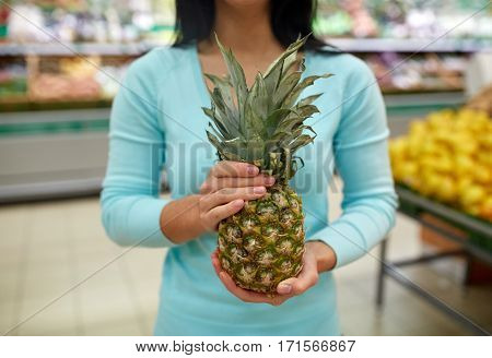 shopping, sale, food, consumerism and people concept - woman with pineapple at grocery store