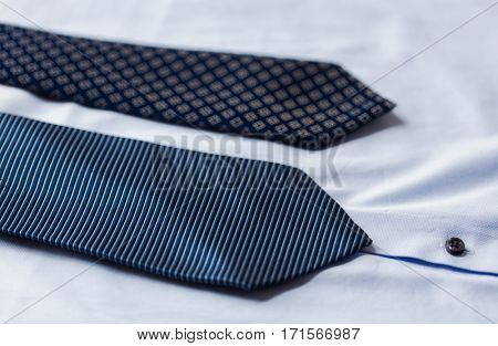 clothing, formal wear, fashion and objects concept - close up of shirt and patterned ties
