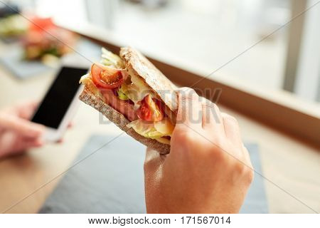 food, dinner, eating and people concept - hand with salmon panini sandwich with tomatoes and cheese at restaurant