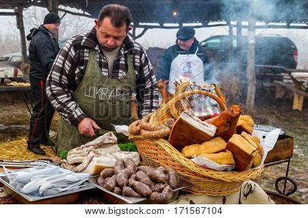 Hecha Ukraine - February 11 2017: Cook one of the teams of butchers cutting smoked bacon during the 11th International gastronomic festival of butchers in the village Hecha.