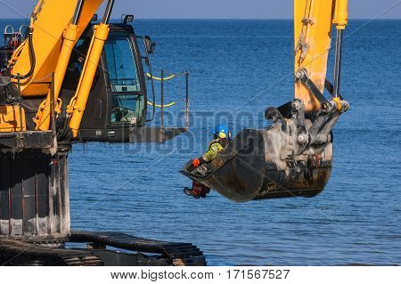 EXCAVATOR - The machine on the sea coast of exports worker ashore