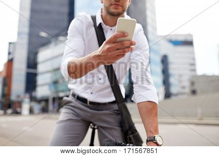 business, people, communication, technology and lifestyle - man texting on smartphone with fixed gear bike on city street
