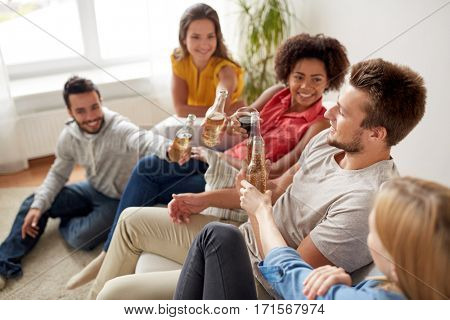 friendship, communication and people concept - group of happy friends with drinks talking at home