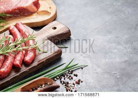 Sausages, meat and ingredients for cooking. View on stone table with copy space