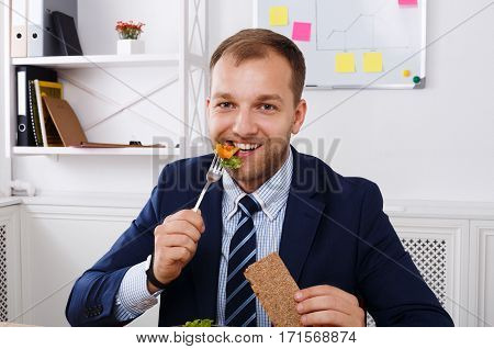 Man has healthy business lunch in modern office interior. Young handsome businessman at working place, eat vegetable salad, diet concept.
