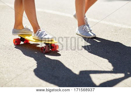 summer, extreme sport and people concept - feet of teenage couple riding short modern cruiser skateboard on road