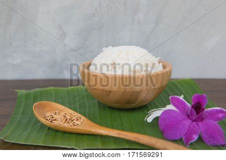 Cooked rice in bowl on green banana leaf and paddy in spoon and orchid .