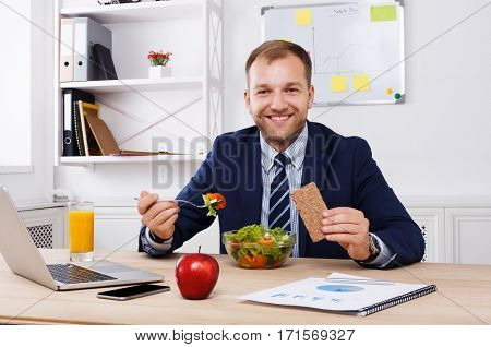 Man has healthy business lunch of vegetable salad and apple in modern office. Young handsome businessman at working place, looking at camera, diet and eating right concept.