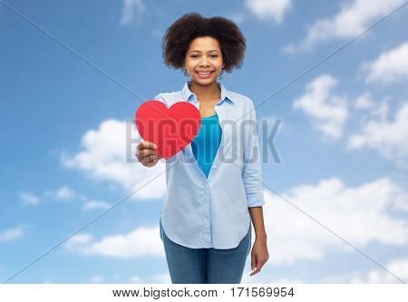 people, love, valentines day and health concept - happy african american young woman with red heart shape over blue sky and clouds background