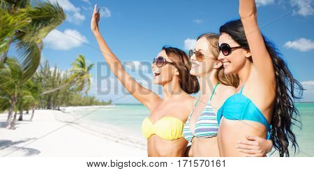 summer holidays, travel, people and vacation concept - happy young women in bikinis and shades hugging and waving hands over exotic tropical beach with palm trees and sea shore background
