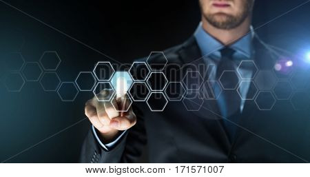 business, people, future technology, network and cyberspace concept - close up of businessman in suit touching virtual reality screen with hexagonal projection over dark background