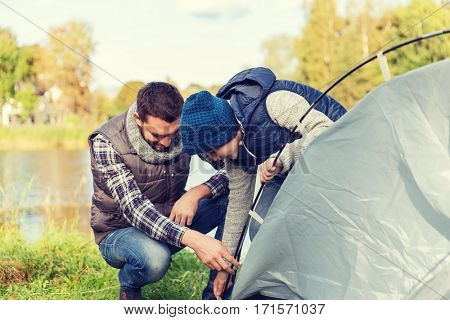 camping, tourism, hike, family and people concept - happy father and son setting up tent outdoors