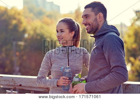 fitness, sport, people and lifestyle concept - smiling couple with bottles of water outdoors