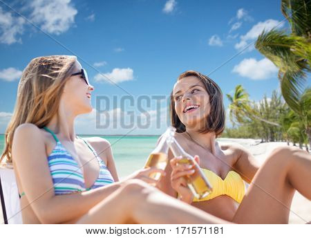 summer holidays, vacation, travel and tourism people concept - smiling young women with drinks sunbathing over exotic tropical beach background