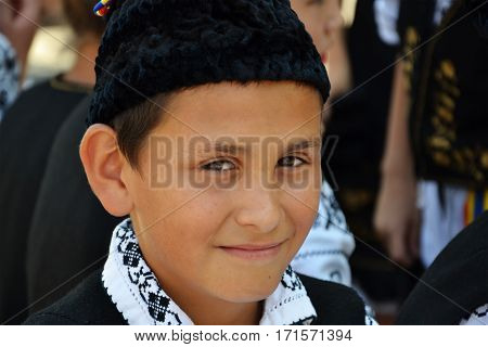CLUJ-NAPOCA ROMANIA - AUGUST 04 2012: Young boy dressed in Romanian traditional folk costumes on the street