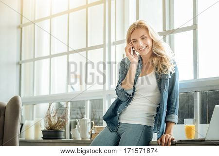 Keep in touch. Smiling young pretty woman talking on a cellphone and drinking juice while spending time at home.