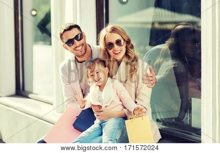 sale, consumerism and people concept - happy family with little child and shopping bags at shop window in city