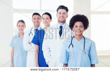 hospital, profession, people and medicine concept - group of happy doctors at hospital
