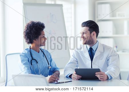 hospital, profession, people and medicine concept - two happy doctors with tablet pc computer meeting and talking at medical office