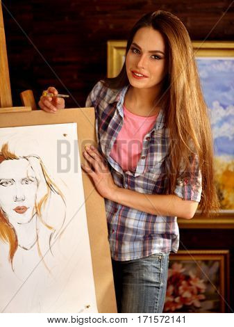 Artist painting on easel in studio. Girl teach paints portrait of woman with brush her students. Female painter seen from behind. She talk about choice of brushes. Indoor home interior for handmade