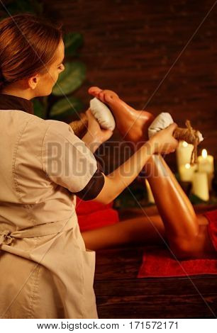 Feet massage with Thai reflexology. Cropped shot of foot reflexology. Body part of female hand and leg on candels background. Masseuse in foreground.