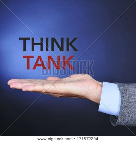 the hand of a young caucasian man wearing a gray suit and the text think tank on a black background lightened in blue