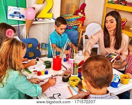 Children painting and drawing in kids club. Craft lesson in primary school. Kindergarten teacher who smiling help small students. Kid boy and girl coloring picture on table in class. Group people work