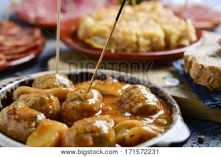 closeup of a plate with meatballs with cuttlefish and some plates with an assortment of different spanish cold meats such as serrano ham, chorizo or cured tenderloin, and a spanish omelette on a table