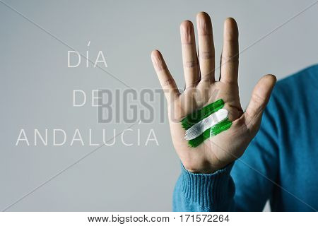 the text Dia de Andalucia, Day of Andalusia in Spanish, and the flag of Andalusia, Spain, painted in the palm of a young caucasian man