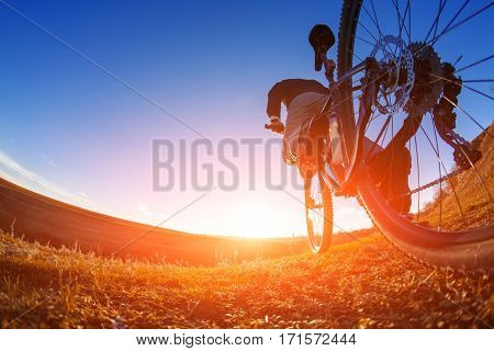 low angle view of cyclist standing with mountain bike on trail at sunset. Fisheye. Beautiful landscape with blue sky and hill. Travel in the countryside. Sport's lifestyle.