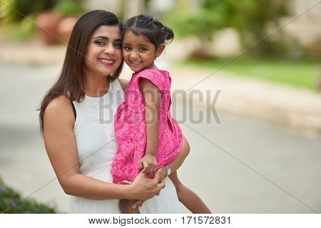 Lovely portrait of Indian family: beautiful middle-aged woman with wide smile holding her cute little daughter in arms against blurred background