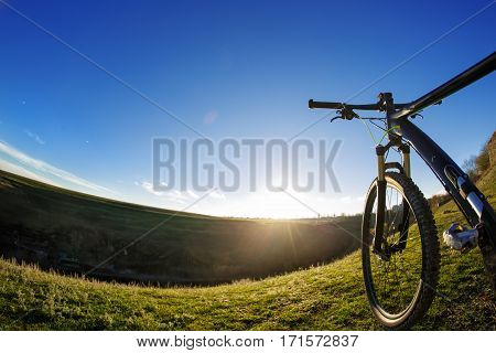 An old bike on journeys. Going up hills on small roads between green fields with blue sky. Sunny day. Wild angle and fisheye. Beautiful landscape. Horizon. Detail of the bicycle. Wheel and rudder. Countryside.