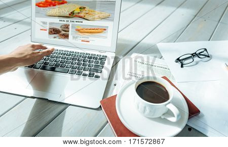 Creative and hardworking. Close up of young pretty ambitious womans hands using laptop and drinking coffee while working at home.