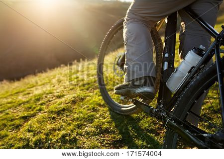 closeup of rear wheel sports mountainbike rides on the hill. Legs and shoes. Detail of the bicycle. Wheel. Landscape with field and sun. Green grass. Travel in the countryside.