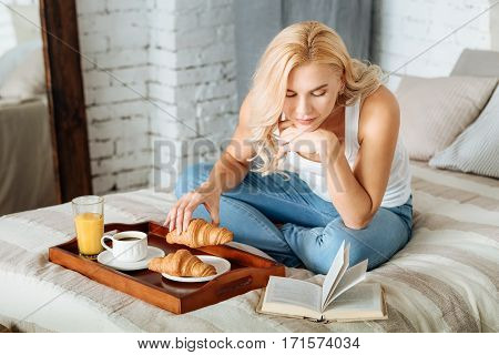 Sweet weekends. Joyful young pretty woman reading book while sitting in bed and drinking coffee with croissants.