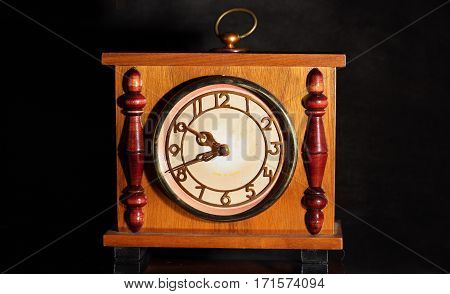 antique clock photographed against a black background